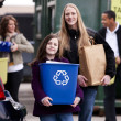 Volunteer employee helping girls at recycling center — Stock Photo #21360641