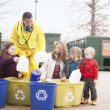 Volunteer employee helping girls at recycling center — Stock Photo