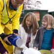 Man helping girls at recycling center — Stock Photo