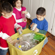 Hispanic siblings recycling together - Stock Photo