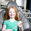 Smiling girl sitting in a dentist chair holding a giant toothbrush — Stock Photo