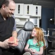 Dentist showing little girl how to brush teet — Stock Photo #21360811