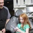 Stock Photo: Dentist showing little girl how to brush teet