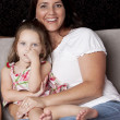 Happy mother and daughter on sofa - Stock Photo