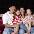 Stock Photo: Joyful family with two сhildren playing on sofa