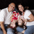 Happy family with two hildren playing on sofa - Stock Photo