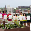 Diverse children by urban rooftop garden holding blank signs - Stockfoto