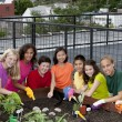 Group of ethnically diverse children planting urban rooftop garden — Stock Photo #21360971