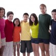 Smiling children of different ethnicities posing in colorful shirts - Stockfoto