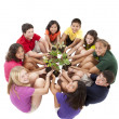 Diverse group of preteens sitting in a circle and holding plants - Stock Photo
