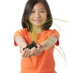 Asian little girl holding green plant — Stock Photo #21361079