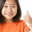 Asian girl showing her approval with a thumbs up — Stock Photo