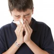 Teen boy is blowing his nose — Stock Photo
