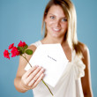 Pretty young woman holding an invitation and flowers — Stock Photo