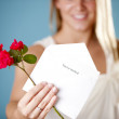 Young woman holding an invitation and flowers — Stock Photo