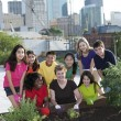 Stock Photo: Children of different ethnicities planting with an adult