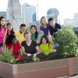Children of different ethnicities gardening with an adult  — Stock Photo