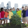 Stock Photo: Children of different ethnicities standing proudly by garden they planted