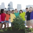 Children of different ethnicities standing proudly by the garden they planted — Stock Photo #21362431