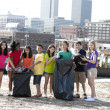 Group of  children of different ethnicities picking up trash in an urban area - Stock Photo