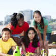 Group of children of different ethnicities working together to plant a garden - Stock Photo