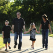 Full length caucasian family walking in the park — Stock Photo