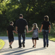Full length caucasian family walking in the park - Stock Photo
