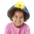 Smiling african american little girl with flowered hat — Stock Photo #21362951