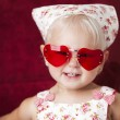 Headshot of smiling toddler girl wearing heart sunglasses - Stock Photo