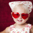 Headshot of smiling toddler girl wearing heart sunglasses — Stockfoto