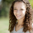 Cute teenage girl with curly hair in the park — Stock Photo