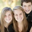 Stock Photo: Image of three smiling caucasiteenage siblings