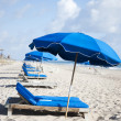 Blue lounge chairs and umbrellas on a beach — Stock Photo
