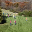 Large group of boys and girls running down a beautiful hillside - Stock Photo