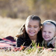 Two caucasian sisters lying down outdoors — Stock Photo