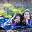 Caucasian sisters lying down outdoors together — ストック写真