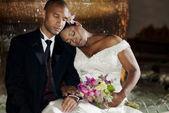 Bruid en bruidegom poseren door een fontein — Stockfoto