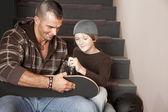 Young adult man helping an adolescent boy with his skateboard — Stock Photo