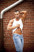 Handsome man showing his abdominal muscles — Stock Photo