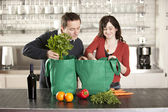 Couple using recycled grocery bags in the kitchen — Foto de Stock