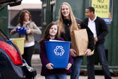 Volunteer employee helping girls at recycling center — Foto Stock