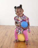 Toddler girl sitting on a yellow ball — Stock Photo