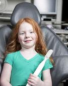 小女孩坐在持有巨型牙刷牙医椅子 — 图库照片