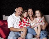 Joyful family with two сhildren playing on sofa — Stock fotografie