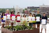 Divers kinderen door stedelijke dak tuin bedrijf leeg tekenen — Stockfoto