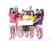 Děti a dospívající drží prázdné přihlásit s palce — Stock fotografie