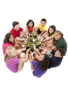 Diverse group of preteens sitting in a circle and holding plants — Стоковое фото