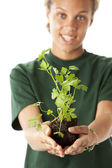Teenage girl holds out a young plant with soil — Stock Photo