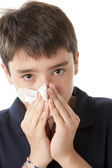 Adolescent boy is blowing his nose — Stock Photo