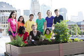 Children of different ethnicities gardening with an adult woman — Stock Photo
